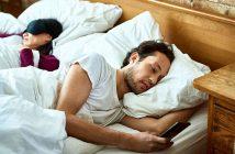 Paar im Bett. Mann mit Handy