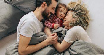 Eltern und Baby liegen glücklich zusammen im Bett