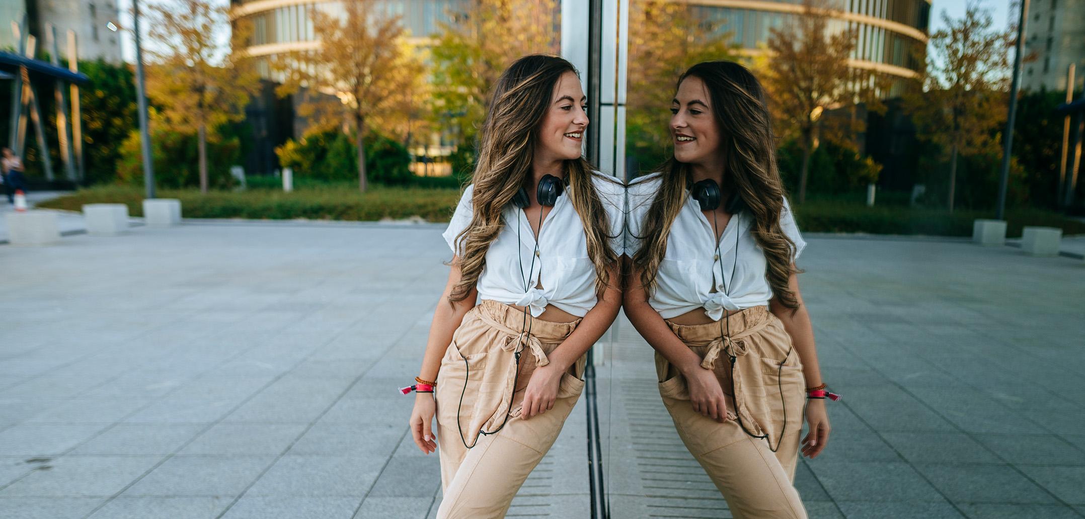 Frau betrachtet glücklich ihr Spiegelbild in einem Fenster