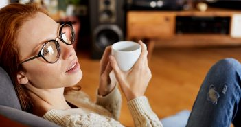 Frau mit Kaffee in der Hand schaut verträumt