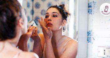 Junge Frau schminkt sich vor dem Spiegel