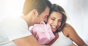 Mann überreicht Frau im Bett ein Geschenk