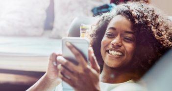 Frau schaut sich glücklich etwas auf ihrem Handy an
