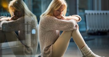 Frau sitzt nachdenklich auf dem Boden und wirkt unglücklich