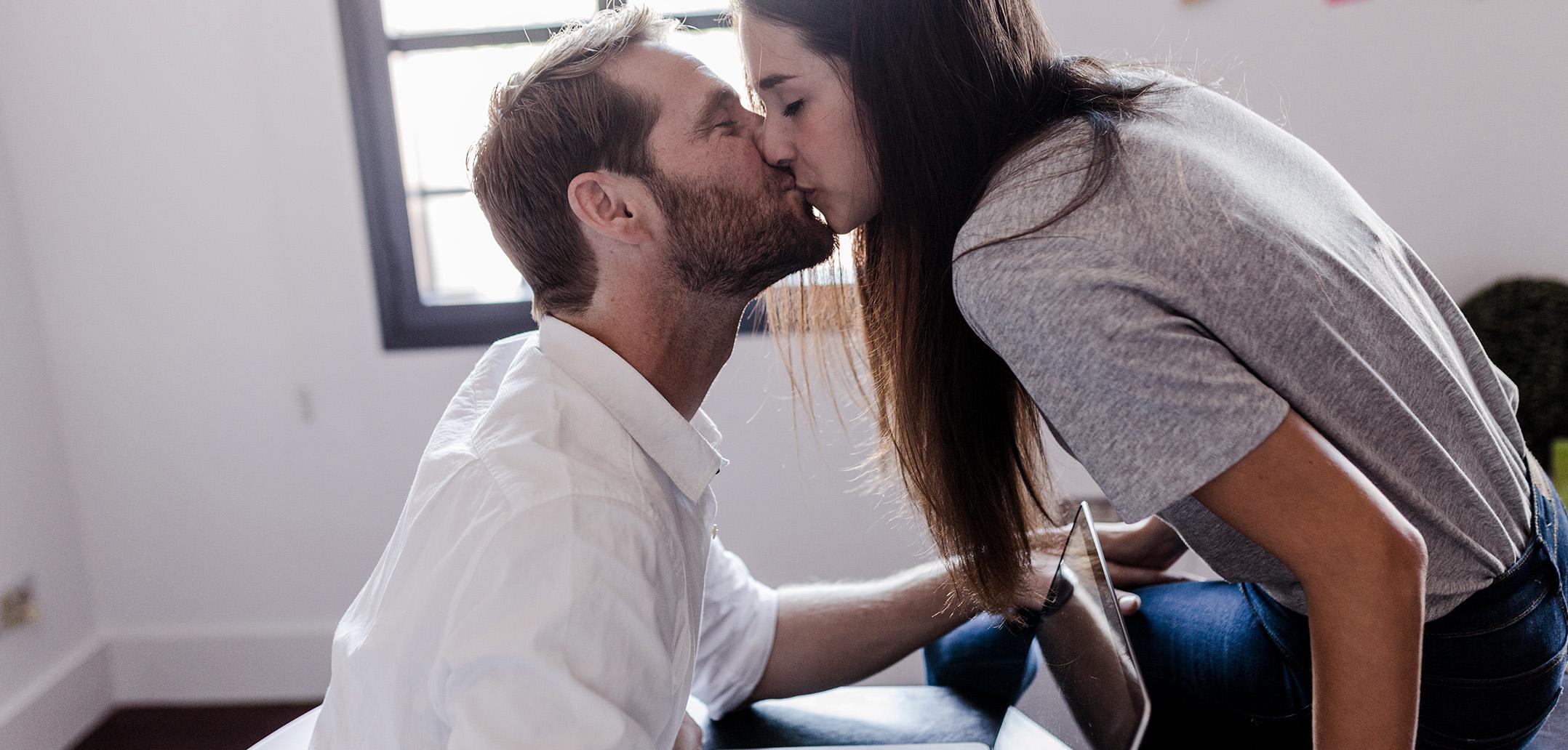 Paar küsst sich liebevoll, während er am Laptop arbeitet