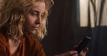Frau schaut traurig auf ihr Handy