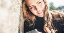 Frau ist am Handy und schaut glücklick verliebt in die Gegend