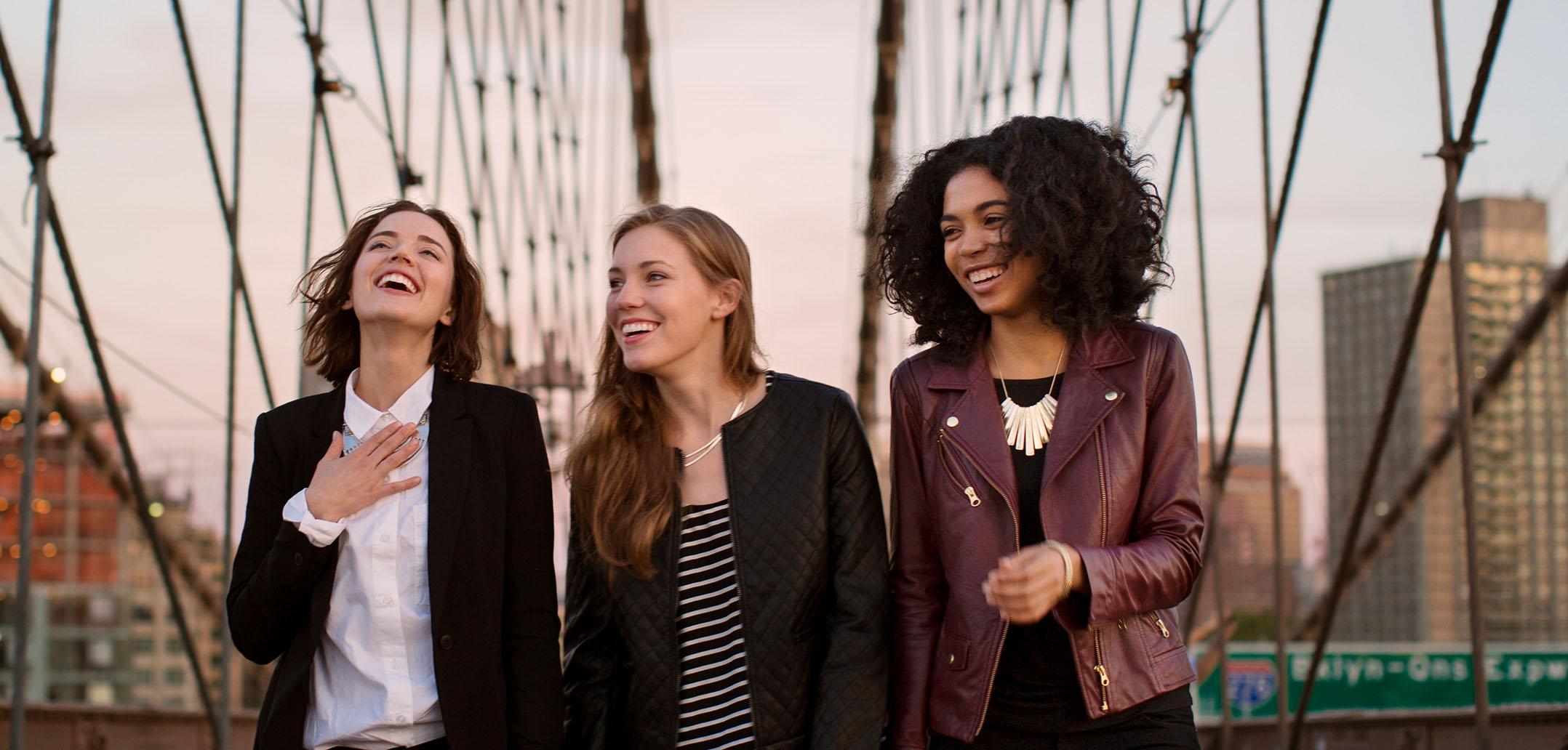 Drei Frauen gehen über die Brooklyn Bridge in New York