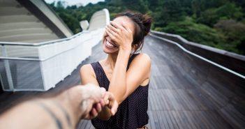 Frau hält sich lächelnd die Augen zu, während sie die Hand eines Mannes hält