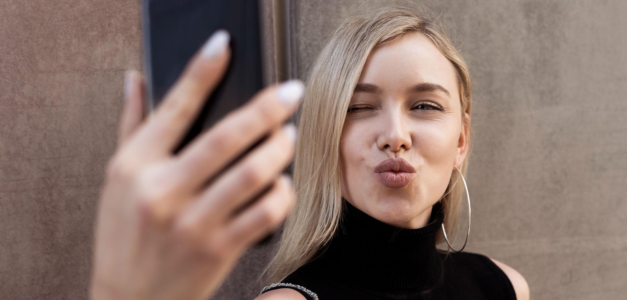 Eine Frau macht ein Selfie mit Kussmund