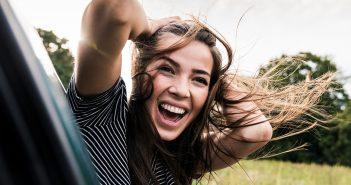 Frau lehnt sich glücklich aus dem Autofenster