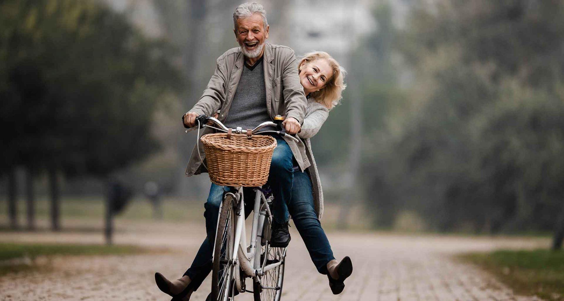Jung gebliebenes Pärchen zusammen auf einem Fahrrad