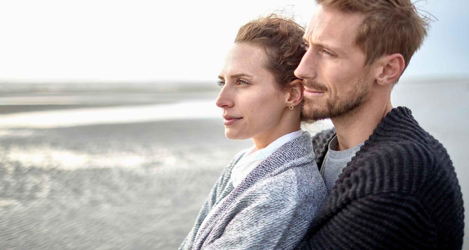 Paar am Strand schaut in die Ferne