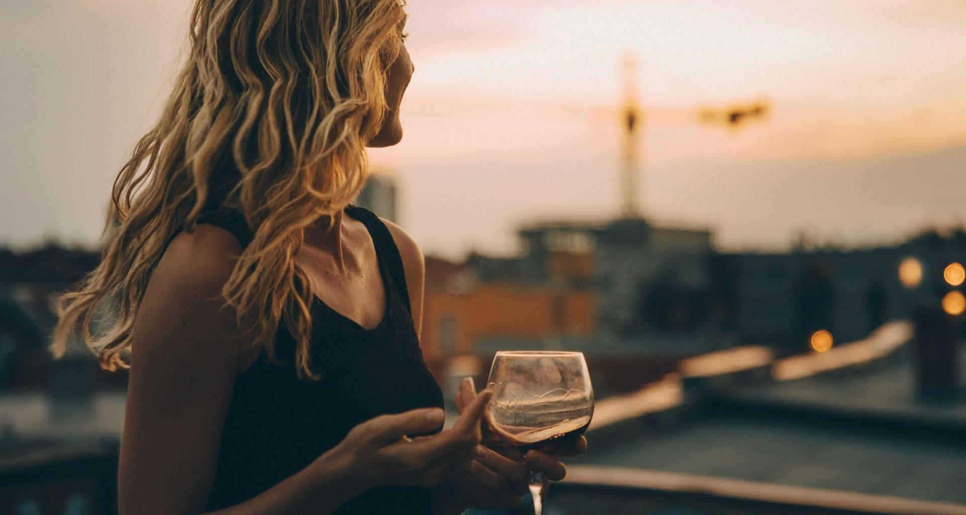 Frau schaut von der Dachterrasse aus in die Ferne